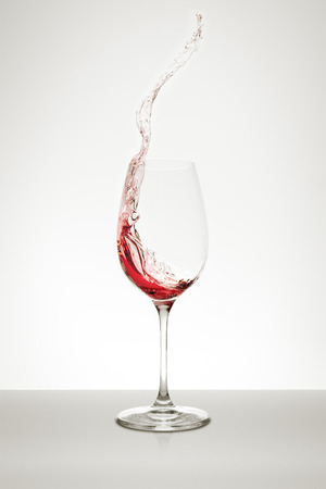 glass of red wine: red wine splashing out of the glass