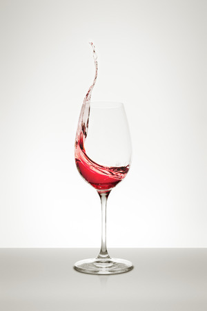 abstract liquor: red wine splashing out of the glass