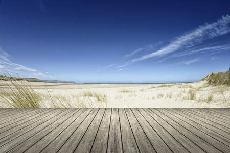 forground: An image of a beach and a wooden jetty in the forground
