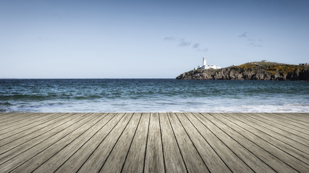 forground: An image of a lighthouse with a wooden jetty in the forground