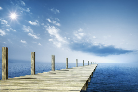 An image of a wooden jetty and the blue ocean background