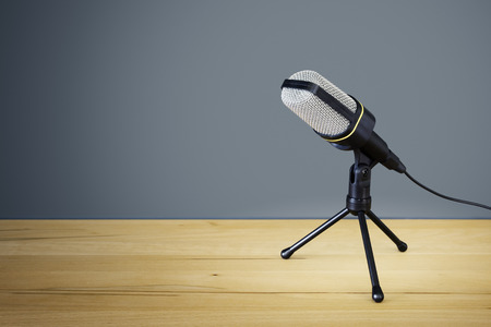 speak: An image of a typical microphone on a wooden desk