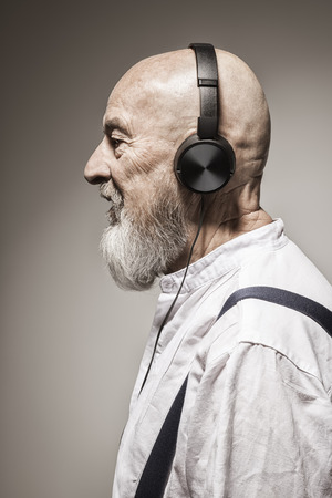 white beard: An image of an elderly bald head man listening to music with headphones Stock Photo