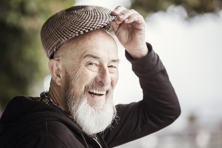 Une image d'un vieil homme avec une barbe en plein air