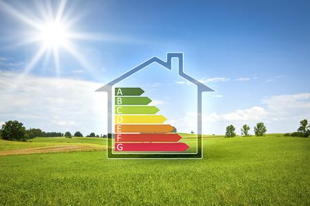 Ein Bild von einem grünen Haus in der Sonne mit der Energieeffizienz Graph Standard-Bild