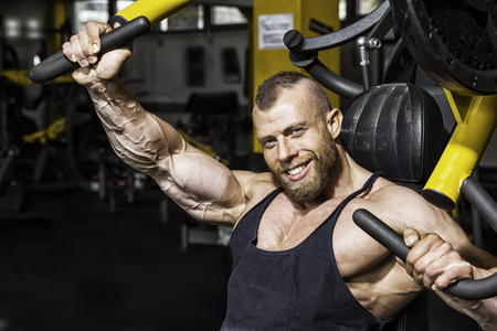 An image of a handsome bearded bodybuilding man doing chest workout Stock Photo