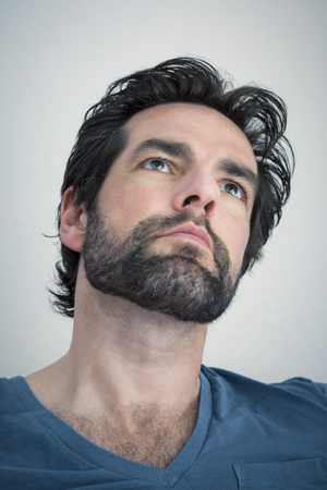 An image of a bearded man looking upwards