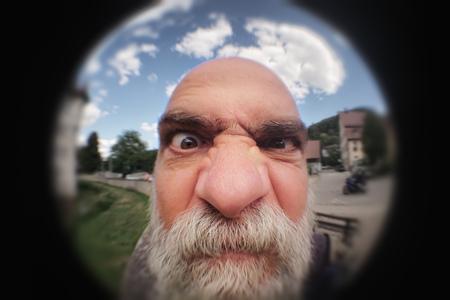 Una imagen de un hombre enojado mirando a una puerta de mirilla