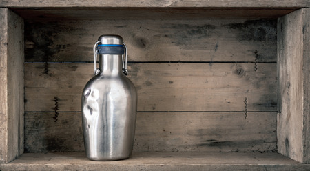 An image of an old dented metal bottle on wooden background Standard-Bild