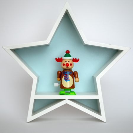 A Christmas decoration white star with funny reindeer figure inside