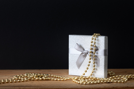A holidays decoration gift box with golden pearls on black Stock Photo