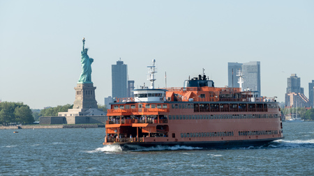 An image of a ferry at downtown New York City with Statue of Liberty Stock Photo
