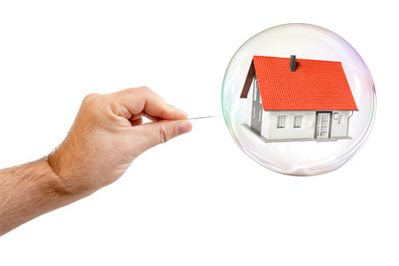 An image of a soap bubble with a house and a males hand with needle to let the dream pop