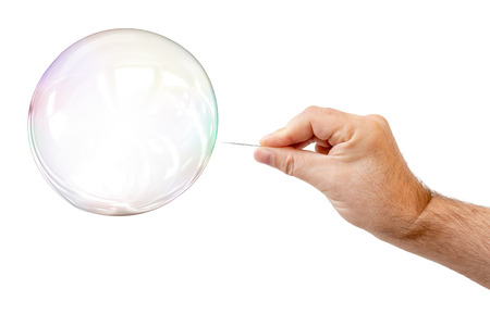 An image of a soap bubble and a males hand with needle to let it pop