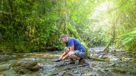 An image of a man doing gold panning in New Zealand Фото со стока