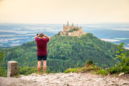 An image of a tourist photographs the Castle Hohenzollern in south Germany Publikacyjne