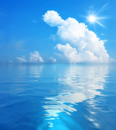 An image of the blue sky with white clouds and sun over the sea