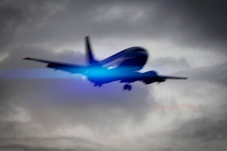 An image of a plane in the sky motion blur with blue light flare