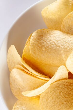 An image of some typical crisps in a white bowl