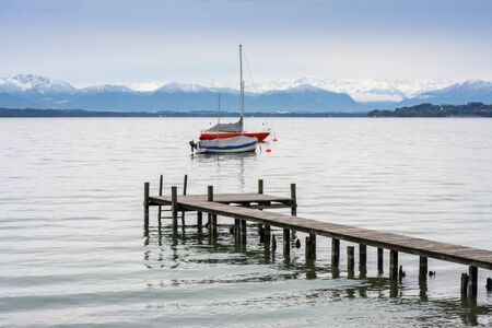 An image of Starnberg lake jetty and boats Alps in winter season