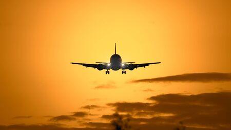 Une photographie d'un avion à réaction dans le ciel au coucher du soleil