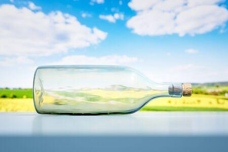 A lying glass bottle landscape scenery background 3D illustration Фото со стока
