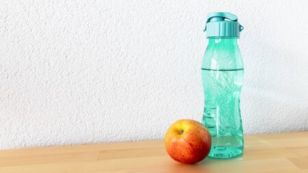 An image of an apple and a water bottle on a wooden table