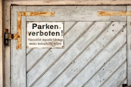 An image of a private no parking sign with german text Illegally parked vehicles will be towed at the owner's expense