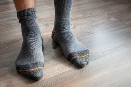 An image of male feet in gray socks on a wooden floor