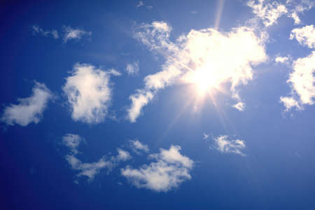 An image of a typical blue sky with sun and clouds background