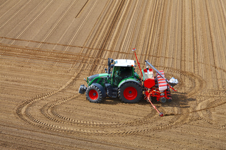 farm tractor sowing in the field in spring