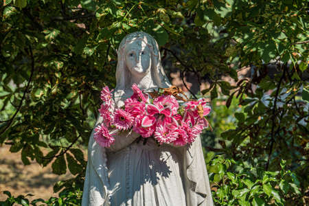 Statue of the virgin maria with some flowers around the neck