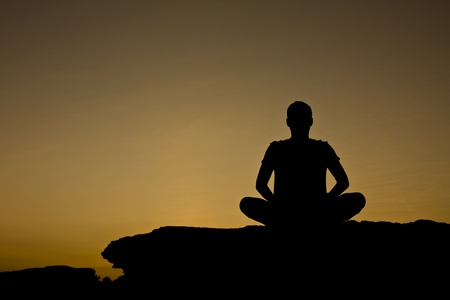 Silhouette of a man in meditation act