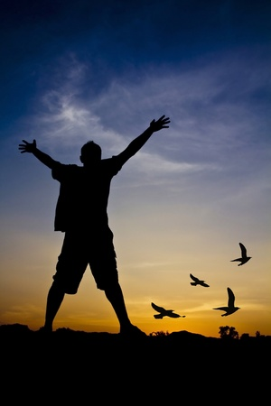 Silhouette of a man with outstretched arms and birds photo