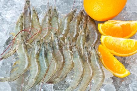 Fresh White shrimps and orange chilled on ice