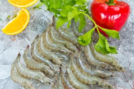 Fresh White shrimps and vegetables chilled on ice Reklamní fotografie