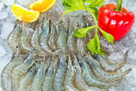 Fresh White shrimps and vegetables chilled on ice Stock Photo