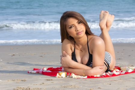 Sexy Asian woman in bikini lying on the beach photo