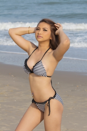 Sexy Asian woman in bikini posing on the beach photo