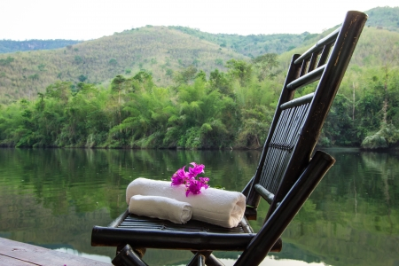 Set of towel and flower on a chair beside the river