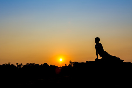 Silhouette of a man in Yoga posting photo