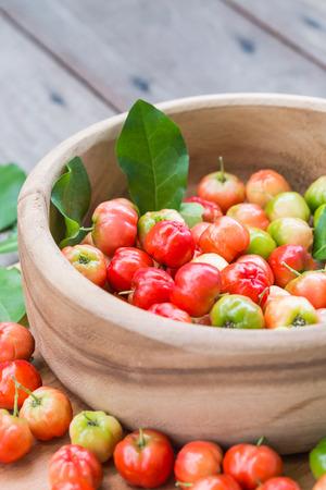 Acerola Cherry on wood bowl Reklamní fotografie