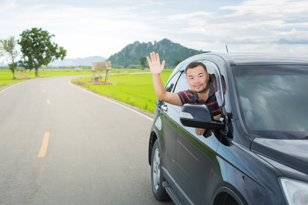 greet: Asian man driving car and show his hand for greet