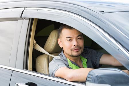 adentro y afuera: Asia hombre sentado en el coche y mirando fuera del coche Foto de archivo
