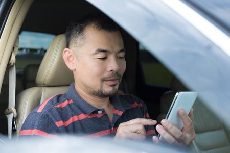 chofer: Hombre asiático uso de teléfonos inteligentes en el coche