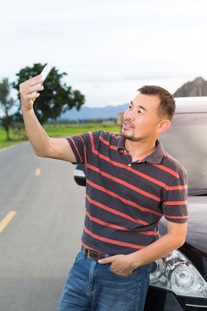Asian man taking selfie on the way