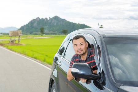 adentro y afuera: Hombre asiático que se sienta en un coche y mirando por la ventana del coche