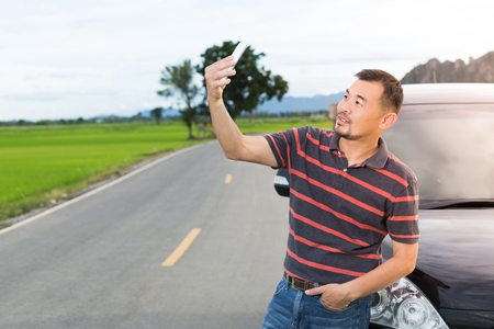 Asian man taking selfie on the way