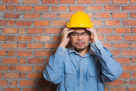 Asian construction technician in stress posting