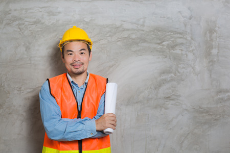 Asian construction technician with paper plan in his hands